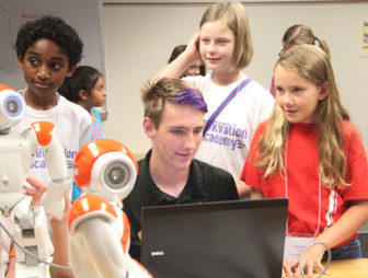 A St. Vrain Valley Schools high school student teaches younger learners to program robots